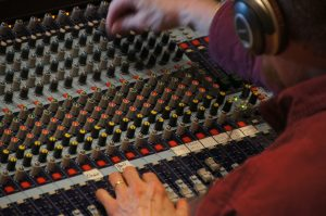 Image of an engineer on a mixing console for beats for budgets.com